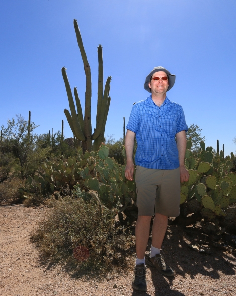 "Stranger 42/100:Sebastian. Like myself, he is a nature enthusiast who was on a photowalk at the Valley View Overlook Trail at Saguaro National Park, West. We had an interesting encounter. It began with my first meeting his mother on the trail. She was a few steps ahead of me and when I caught her, discovered she was a German traveling with her husband and son. They were both was ahead of us on the trail. We caught up to them and reached an exciting subject: a low hanging open flower on a Saguaro cactus that was perfect for picture making. Most flower buds don't appeaer at human eye-level. The cactus don't produce the flowers until the life of the plant is anywhere from 35-75 years old, and they sprout at the top of the plant head, which can range in height from 20+ feet up. I noticed that the son was equipped like me with Canon equipment and he had some extension tubes on his main lens. I wanted to compare exposure notes (it was extremely bright in the 3 'o clock hour of hour meeting). So in my rough German, I began to speak and ask him a question. He appeared to ignore me. Mother put her hand on my shoulder and said in English, ""He can't hear you. He can not hear."" I looked at her and asked, ""He is deaf?"" To which she nodded one time. He looked up and I spoke slowly, because it was evident he was an accurate lip reader. I asked his name in German, and he answered me in perfect English. Meet Sebastien, 43/100. Both of us returned to our respective vehicles and came back with additional lenses: I with my 10-22mm wide and external flash; he with some 100mm macro. We each spent about five minutes studying the flower, and then turned to each other and asked if we could take each others' picture. He wanted to have his photo taken with the wide angle, so he popped his memory card into my camera, and I made this image for him. I asked him to hold on and let me take it once I replaced the memory card with my own. He also took one of me with the same background. Afte"