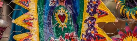 A colorful paper mache folk art piece depicting Saint Guadelopue, also known as the Virgin Mary