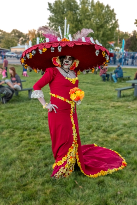 A vertical portrait of a woman in an elaborate Day of the Dead costume