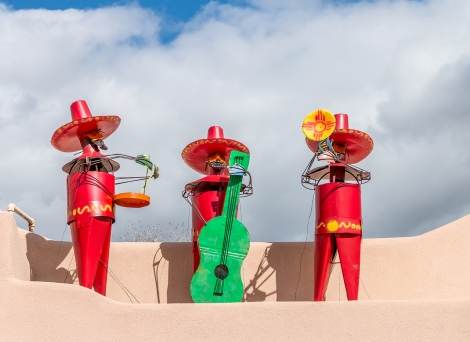 Three tin folk art statues depict a mariachi band playing music