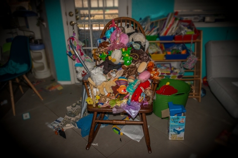 A rocking chair is filled with a toddlers toys