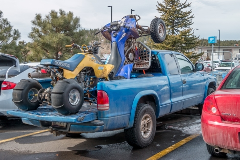 A pickup truck with two ATVs in its flatbed is in a parking space