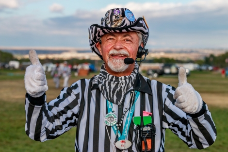 "My 76/100 strangers is a fellow named Bill who described himself as intelligent, joyful and accommodating. Bill is a Zebra, and Chief Launch Director for the Albuquerque International Balloon Fiesta (AIBF). He has been involved with Fiesta for 21 years. He used to live in Albuquerque, but his wife's job moved them away to Tennessee, where during the year he is a business to business consultant. Bill returns dutifully to Albuquerque to perform his mission critical AIBF event job, which shows his passion and commitment for the event. We met during Mass Ascension in an area that was being corded off for a hot air balloon compeition. Bill handed me a card while we were becoming acquainted. On one side is a group portrait of Zebras wearing their black and white dazzle uniforms. On the reverse it says the following: ""The Launch Directors, affectionately known as the ""Zebras"" are volunteers whose job is to safely launch all 600+ balloons at the Albuquerque International Balloon Fiesta. The Zebras are all volunteers who work very hard for the nine days of Fiesta. Without their assistance, it would be close to impossible to get 600+ balloons in the air at the same time. They work hard, are dedicated and enjoy The Zebra life."" Like Bill, all Zebras dress in black and white striped referee uniform tops and each one puts custom flair touches on his or her outfit. Outlandish details are expected, such as zebra themed buttons or pins, and the zebra patterned cowboy hat you see being worn by Bill. Other than their microphone and earpieces for walkie-talkie radio communicaitions, Zebras all wear referee whistles and blow them to direct spectators and foot traffic away from balloon crews setting up the hot air balloon equipment, which includes balloon envelopes, stay lines and baskets. You usually hear them before you see them; which is hard to imagine considering the dazzle they must wear."