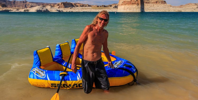 A man with his inflatable raft in Wahweap Bay, Utah