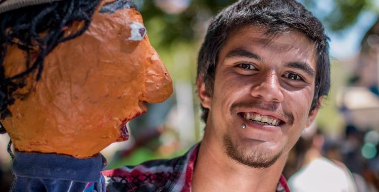 A young man and a papier mache puppet